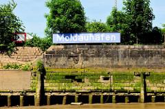 Kaimauer bei Niedrigwasser im Hamburger Hafen - der Bereich bei Hochwasser ist mit Algen bewachsen. Bei Ebbe zeigen sich die Baumstämme, die das Fundament der Kaianlage bilden. Holzdalben sind mit Gräsern bewachsen.