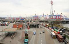 Zollanlage des Hauptzollamts Waltershof - beladene LKW stehen in der Warteschlange um ihre Ladung zu den Containerterminals bringen zu können - im Hintergrund Containerkräne / Hafenanlagen des Waltershofer Hafens.