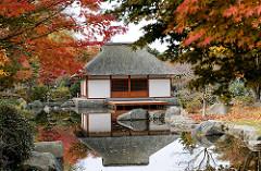 Japanisches Teehaus zwischen rot gefärbten Herbstblättern vom Japanischen Ahorn - Herbstbilder aus Hamburg, Herbstfotos von Planten un Blomen.