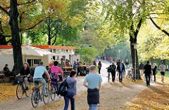 Spaziergang in der Herbstsonne an der Alster in Hamburg St. Georg - Café mit Tischen unter Bäumen.