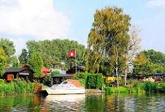 Kleingartenkolonie in Hamburg Rothenburgsort - die Parzellen liegen am Wasser des Bullenhusener Kanals - an einem Anleger liegt ein Sportboot.