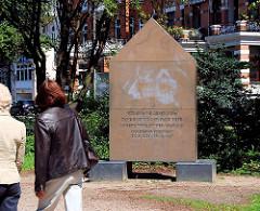 """Denkmal Wolfgang Borchert beim Schwanenwik; Passanten auf dem Alsterweg - Inschrift """"Wir sind die Generation ohne Bindung und Tiefe. Unsere Tiefe ist der Abgrund. Wir sind eine Generation ohne Abschied, aber wir wissen, dass alle Ankunft uns gehört."""