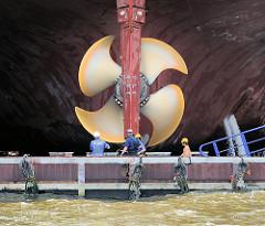 Blick auf die Schiffsschraube eines eingedockten Schiffs im Hafen Hamburgs.