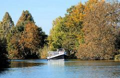 Herbst an der Dove Elbe in dem Hamburger Stadtteil Curslack; eine Barkasse fährt flussaufwärts.