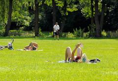 Liegewiese im Hammer Park; Menschen liegen auf der Wiese in der Sonne.