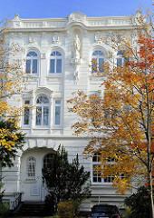 Etagenhaus mit weisser Fassade - Stuck Verzierung an der Hauswand. Strassenbaum im Herbst.