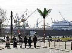 Parc Fiction, Antonipark an der Elbe - Fussgängerinnen mit Kinderkarre - Kreuzfahrtschiff eingedockt.