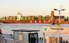 Anleger der Hafenfähre in Hamburg Finkenwerder - ein hochbeladenes Containerschiff passiert die Lotsenstadtion am Seemannshoeft.