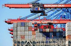 Containerbrücken am Hamburger Terminal Burchardkai - Lascher werden zum Lösen der Container Befestigungen am Heck in einem Stahlkorb entlang bewegt.