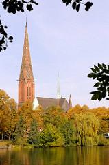 St. Gerturdenkirche in Hamburg Uhlenhorst - Bäume mit Herbstlaub am Ufer des Kuhmühlen-Teichs.
