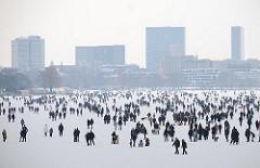 Menschen auf der zugefrorenen Alster - Hamburger Volksfest im Winter - im Hintergrund die Silhouette von Hamburg St. Georg.