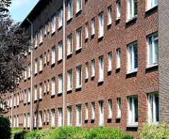 Hausfassade mit Fenstern - weisse Fensterrahmen, rote Klinkermauer - Wohnblock in Hamburg Hamm.