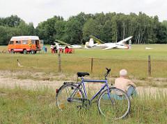 Segelflugplatz Hamburg Boberg - mehrere Segelflugzeugen warten auf ihren Start - ein Radfahrer hat sein Fahrrad abgestellt, sitzt am Rand des Flugplatzes in der Sonne und beobachtet das Treiben.