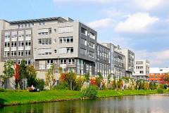 Grünstreifen mit Ruhebänken am Ufer des Mittelkanals in Hamburg Hammerbrook - Wohnungen am Wasser des Kanals.