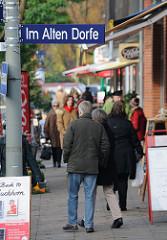 Einkaufsstrasse in Hamburg Volksdorf - Strasse IM ALTEN DORFE - Passanten auf dem Fussweg.