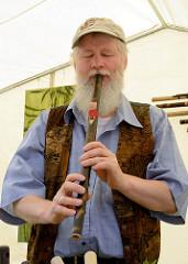Biohof Gut Wulksfelde - Bauernmarkt. Aussteller präsentieren ihre Bioprodukte und Kunsthandwerk.  Ein Hersteller von Bambusflöten aus Hamburg spielt auf einem seiner Instrumente.