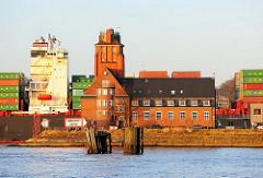 Das Containerschiff HATTA Höhe Lotsenstation Seemannshöft - die Aufbauten und Containerladung des Frachtschiffs haben die gleiche Höhe wie das historische Lotesengebäude in Hamburg Waltershof.