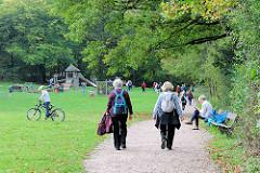 Grünanlage und Spielplatz an der Alster in Hamburg Wohldorf-Ohlstedt; Kinder spielen - Spaziergängerinnen auf dem Alsterwanderweg.