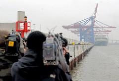 Fernsehteam beim Filmen der neuen Kaimauer am Waltershofer Hafen - Containerbrücken Burchardkai im Hamburger Nebel.