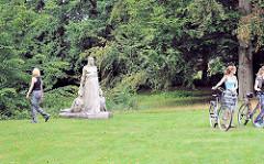 """Skulptur """"Schicksal"""" ParkbesucherInnen auf der Wiese. Bilder vom Hamburger Parkfriedhof Ohlsdorf."""