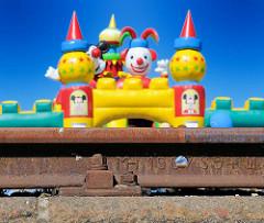 rostige Schiene am Kai des Harburger Binnenhafens; bunte Figuren einer Hüpfburg beim Hafensfest.