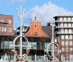 Dekorelemente des Zollzauns am Zollkanal - im Hintergrund re. ein Ausschnitt vom Giebel der Polizeiwache am Klingberg sowie dem Chilehaus.