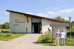 Haus der Wilden Weiden im Naturschutzgebiet Höltingbaum - Ausstellungsgebäude der Stiftung Naturzschutz Schleswig Holstein. Zwei WanderInnen stehen vor dem Übersichtsplan des Naturschutzgebietes.