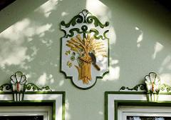 Stuckdekor an der Fassade eines Hauses - vergoldete Ährengarbe und Sichel - Fotos aus Hamburg GUT MOOR.