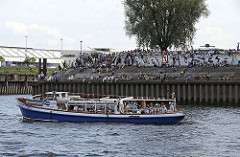 Aussichtsplattform auf Steinwerder Elbufer - eine vollbesetzte Barkasse fährt auf der Elbe.