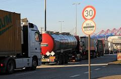 """Warteschlage von Lastkraftwagen vor der Zollabfertigung beim Hauptzollamt Hamburg Waltershof. Verkehrschilder - Geschwindigkeitsbegrenzung auf 30 km/h und """"Zoll - Douane"""". Im Hintergrund Contaienbrücken des Containerterminals EUROGATE."""