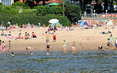 Sandstrand an der Elbe - Sommerszene am Elbufer - Sonnenschirme und Badende im Elbwasser - Fotos aus Hamburg Othmarschen.