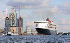 Die Queen Mary 2 hat ihren Liegeplatz am Cruisecenter in der Hamburger Hafencity verlassen und befindet sich in Höhe der Baustelle der Elbphilharmonie.
