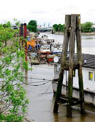 Blick auf das Potsdamer Ufer des Hamburger Spreehafens - im Vordergrund Holzdalben und ein trockegefallenes Hausboot - Schlick bei Ebbe.