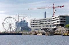 Blick aus dem Baakenhafen im Hamburger STadtteil Hafencity Richtung Magdeburger Hafen; rechts die Baustelle der HafencityUniversität und entstehende Brücke über den Baakenhafen; im Hintergrund ein Riesenrad und die Baustelle der Elbphilharmonie.