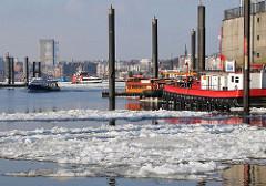 Der Hamburger Hafen im Winter - Eis und Schiffe an der Kaimauer am Baumwall, Vorsetzen.