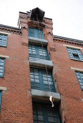 Historischer Speicher in einem Hinterhof von Hamburg St. Pauli - mehrere Speicherstockwerke / Böden mit einer Winde unter dem Dach.