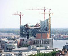 Baustelle der Hamburger Elbphilharmonie im Stadtteil Hafencity - im Hintergrund die histoirschen Hafenkräne und Industriearchitektur am Hansahafen.