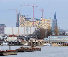 Blick über den Travehafen in Hamburg Steinwerder - beladene Schuten liegen an Dalben - lks. die Ellerholzschleuse, rechts Gebäude der Wasserschutzpolizei; im Hintergrund Baustelle der Elbphilharmonie und Turm der St. Nikolaikirche.