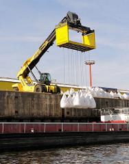 Radkran mit einer Transportvorrichtung, mit der eine Ladung von  zehn Schüttgut - Säcken an Land transportiert werden können - Fotos von der Arbeit im Hafen Hamburgs.