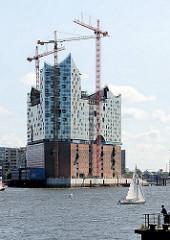 Bausstelle der Hamburger Elbphilharmonie  - ein Segelschiff kreuzt auf der Elbe.