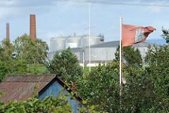 Hamburg Flagge im Kleingartengelände - Öltanks und Schornsteine einer Erdöl-Raffinerie im Harburger Seehafen.