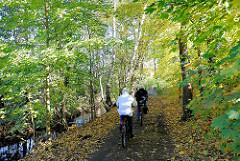 Kollauwanderweg - Spazierweg entlang des Niendorfer Bachs - Fahrradfahrer fahren auf dem matschigen Weg; lks. die Kollau - hier Grenzfluss zwischen Hamburg Niendorf und Lokstedt.
