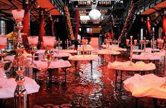 Das Hochwasser hat die Vorbereitung einer Feier in der Fischaktionshalle unterbrochen; die Tische sind festlich geschmückt - das Wasser steht auf dem Boden der Eventlocation.
