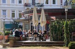 Strassencafe in der Sonne - Gäste sitzen in Hamburg Ottensen an der Eulenstrasse.
