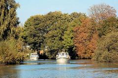 Zwei Sportboote, Motorboote auf der Dove-Elbe in den Hamburger Vierlanden / Stadtteil Curslack; die Bäume am Flussufer sind herbstlich gefärbt.