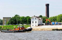 Blick über die Billwerder Bucht beim Sperrwerk - ein Schlepper fährt in die Bucht ein; hinter der Villa Hintzpeter der historische Wasserturm des Stadtteils Rothenburgsort.