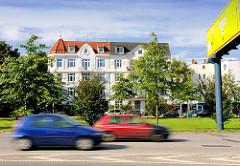 Blick über die Hauptverkehrsstrasse mit schnell fahrenden Autos zu mehrstöckigen Gründerzeitgebäuden im Hamburger Stadtteil Gross Borstel.