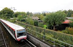U-Bahnlinie am Rande eines Kleingartens in Hamburg Barmbek Nord - ein Zug der Hamburger Hochbahn fährt Richtung Fühlsbüttel Nord.
