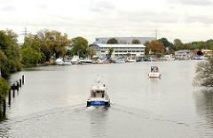 Motorboote fahren aus der Tatenbergerschleuse in die Dovelebe ein - im Hintergrund ein Sportboothafen in Hamburg Moorfleet.