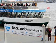 Die Hafenfähre Hafencity legt am Anleger Dockland / Fischereihafen an - Passagiere stehen auf dem Oberdeck im Freien; Bilder aus der Hansestadt Hamburg.